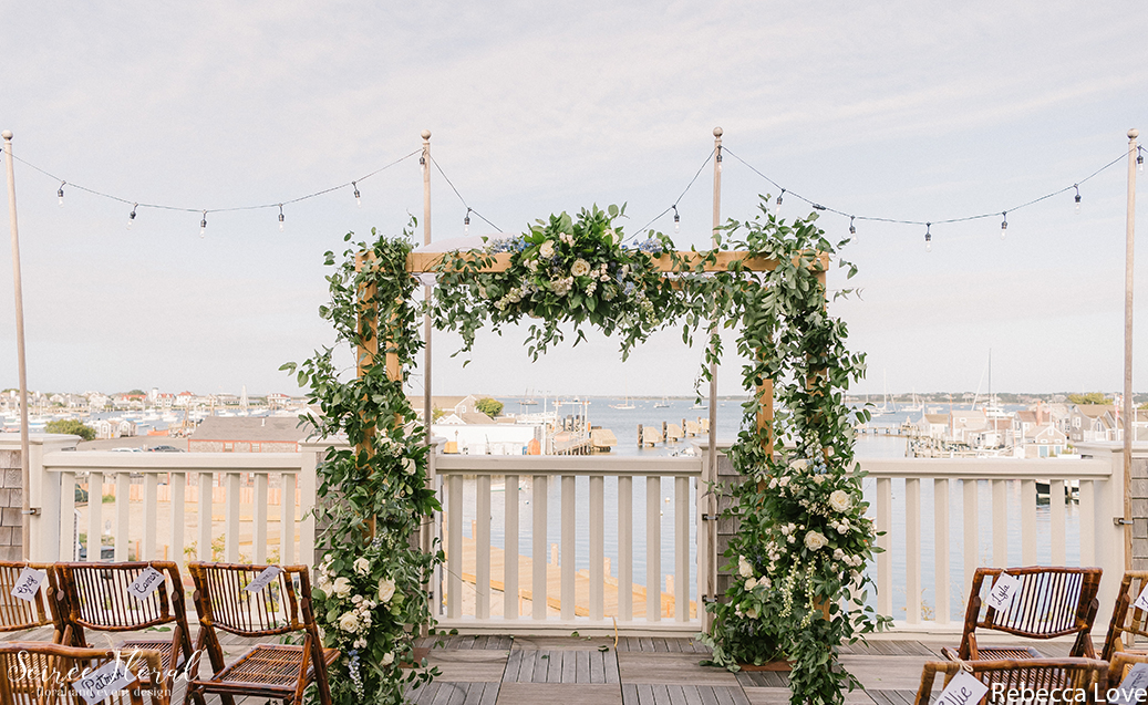 Chuppah with White and Blue Blooms on the Dreamland Harborside Terrace. Photo by Rebecca Love Photography.