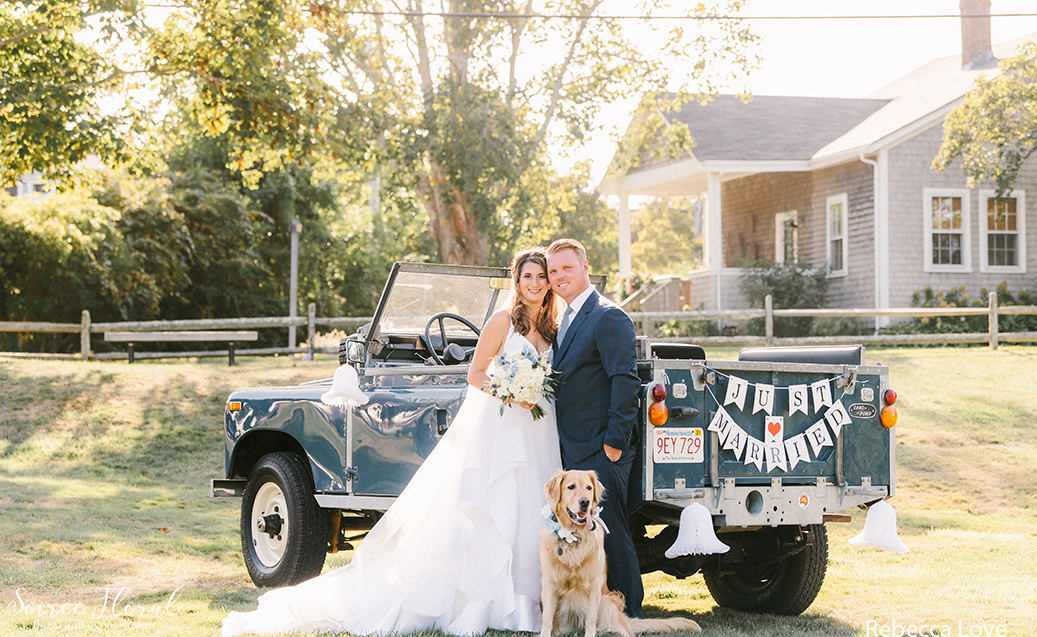 """Bride and Groom Posing with Vintage Range Rover with """"Just Married Sign"""". Photo by Rebecca Love Photography."""