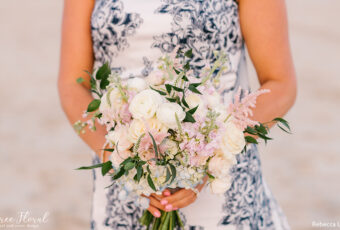 Blush Bridal Bouquet Against Blue and White Floral Wedding Gown